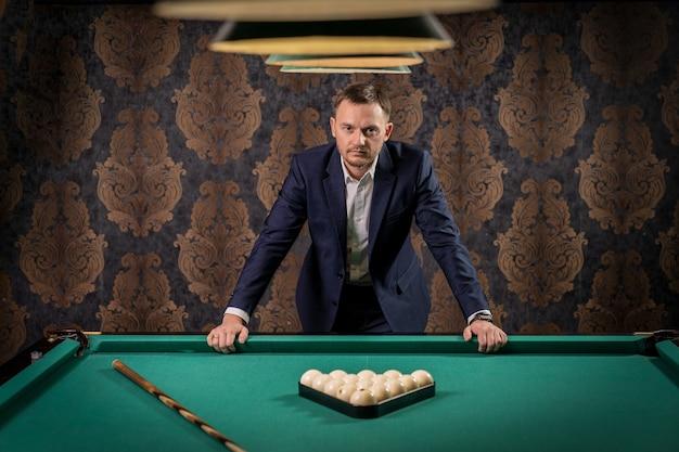 Un uomo sta in piedi a un tavolo da biliardo su cui vengono preparate palline e una stecca per il gioco