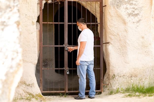 Un uomo si trova di fronte a una porta chiusa di metallo con una limitazione del divieto di lucchetto a causa del coronavirus