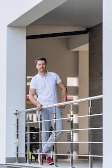 L'uomo sta vicino alla ringhiera di metallo. abito bianco. uomo adulto moderno. uomo alla moda.