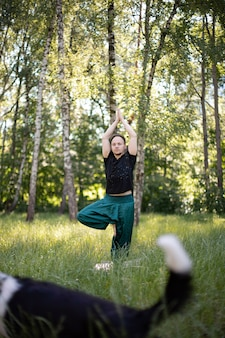 L'uomo sta in una posa che fa yoga con il cane nel parco su erba verde green