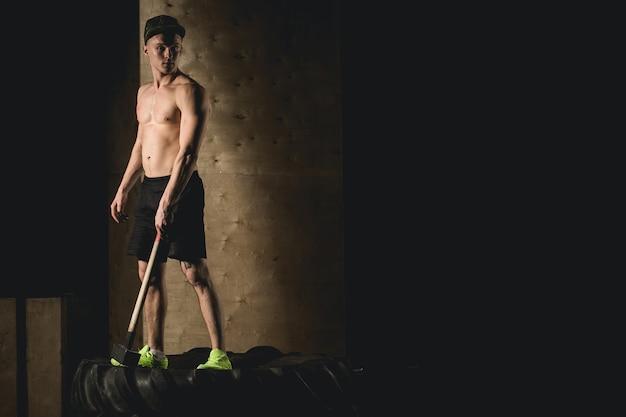 L'uomo sta ruota pneumatico con martello slitta crossfit training