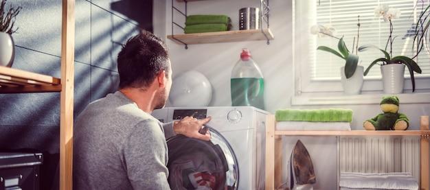 Uomo che avvia lavatrice