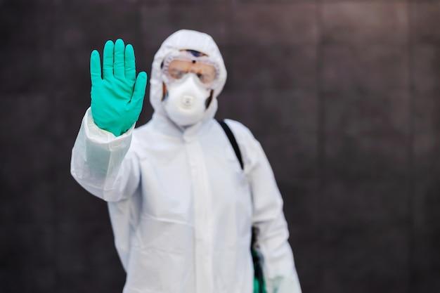 Uomo in uniforme sterile in piedi all'aperto e tenendo la mano come un segnale di stop durante la corona.