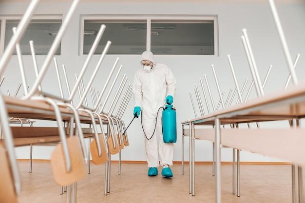 Uomo in uniforme sterile, con guanti e maschera che tiene spruzzatore e spruzzatura con scrivanie e sedie disinfettanti in aula