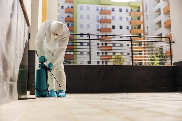 Uomo in uniforme protettiva bianca sterile con guanti di gomma che pompano spruzzatore con disinfettante e impediscono la diffusione del virus corona.