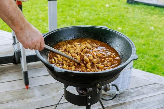 Uomo che mescola la carne di pollo nel calderone di ferro