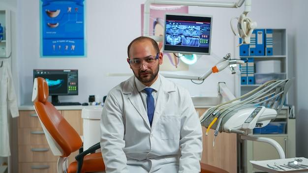 Stomatologo uomo parlando alla videocamera seduto su una sedia in clinica dentale con assistente in background. medico di odontoiatria che guarda la webcam che spiega il trattamento mentre l'infermiera sta lavorando al computer