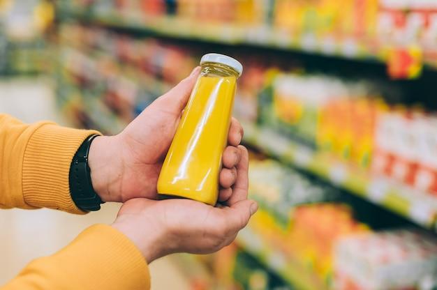 L'uomo in un negozio tiene in mano una lattina di succo d'arancia sullo sfondo di un rack.