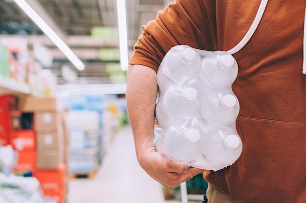 Un uomo in un negozio tiene un pacchetto di acqua in bottiglia pulita e trasparente.