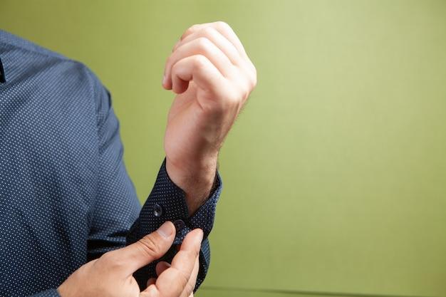 Un uomo raddrizza un bottone sulle maniche su uno sfondo verde