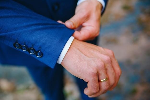 L'uomo raddrizza il polsino della giacca blu con il suo primo piano della mano