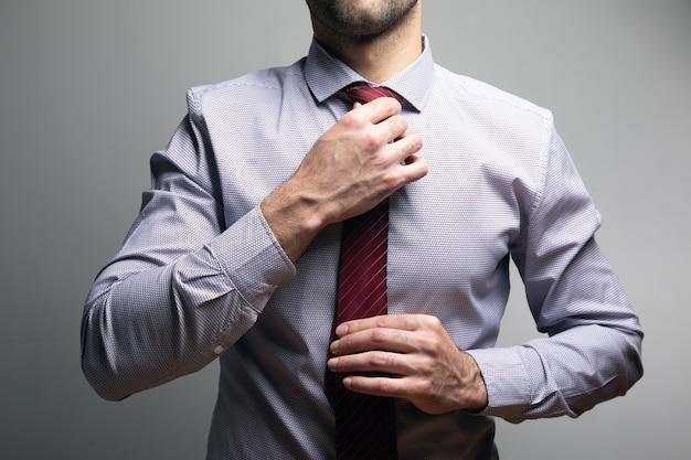 L'uomo raddrizza la sua cravatta su un muro grigio.