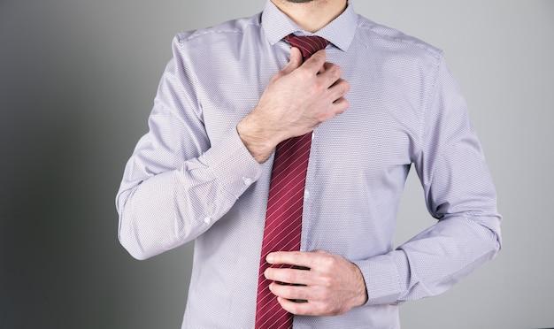 L'uomo raddrizza il suo tieman raddrizza la sua cravatta su una superficie grigia