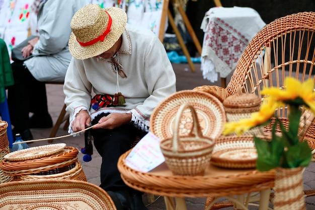 Un uomo con un cappello di paglia intreccia da una vite. prodotti di paglia. artigianato etnico. l'uomo maestro di paglia