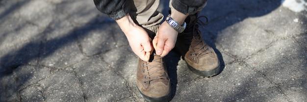 L'uomo sulla strada si chinò e legò i lacci delle scarpe. passeggiata nel parco durante la quarantena. l'aria fresca attiva le difese dei bodys. emergenza per violazione pandemica. ragazzo in abiti casual è in piedi sul marciapiede