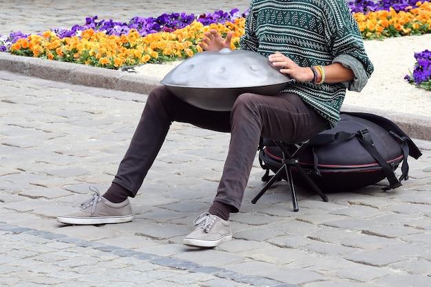 L'uomo della strada suona uno strumento a percussione appeso