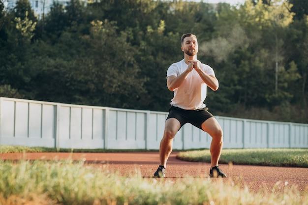 Uomo che si allunga prima dell'allenamento allo stadio