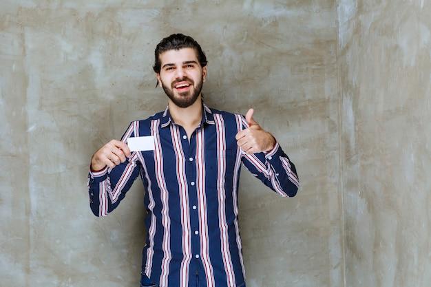 Uomo in camicia a righe che tiene il suo biglietto da visita e si gode la sua nuova posizione
