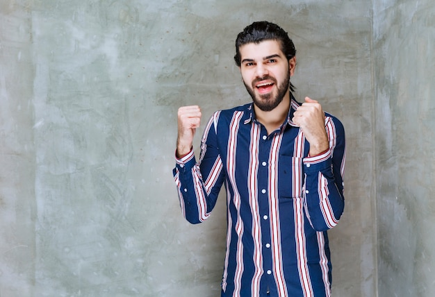 Uomo in camicia a righe che mostra i suoi pugni e si sente forte.