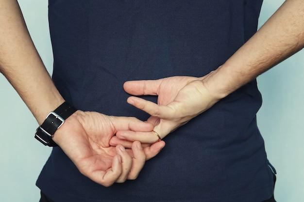 Un uomo che lotta per rimuovere l'anello nuziale dal dito tenendosi per mano dietro la schiena. concetto di tradimento. il marito tradisce la moglie. moglie infedele.