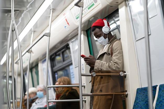 Uomo in treno della metropolitana indossare la maschera per il viso utilizzando il cellulare
