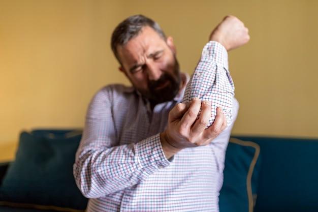 Uomo che soffre di dolore al gomito
