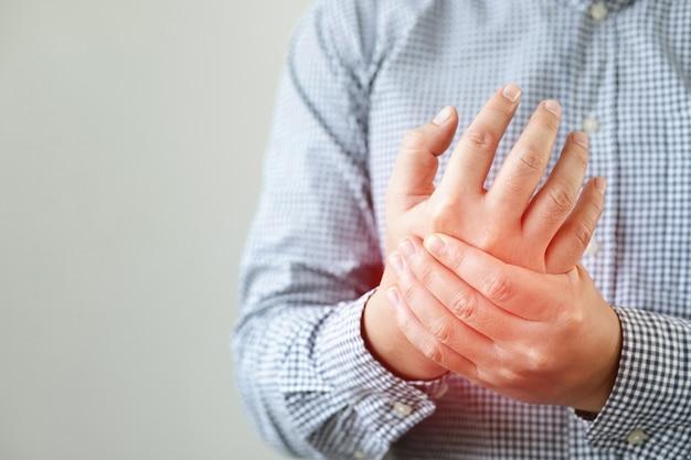 Uomo che soffre di dolore alla mano, dolore alle ossa
