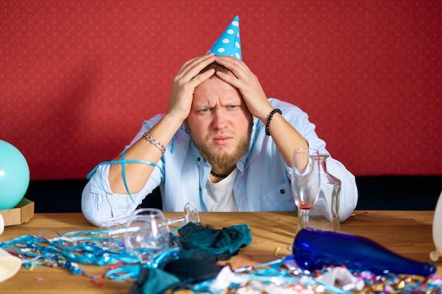 Uomo che soffre di postumi di una sbornia a tavola con un berretto blu in una stanza disordinata dopo la festa di compleanno