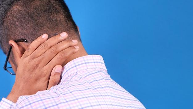 Uomo che soffre di dolore al collo o alla spalla sulla parete blu