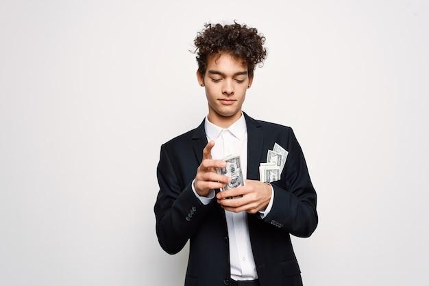 Uomo in giacca e cravatta un pacco di soldi nelle mani di un uomo d'affari con fiducia in se stessi