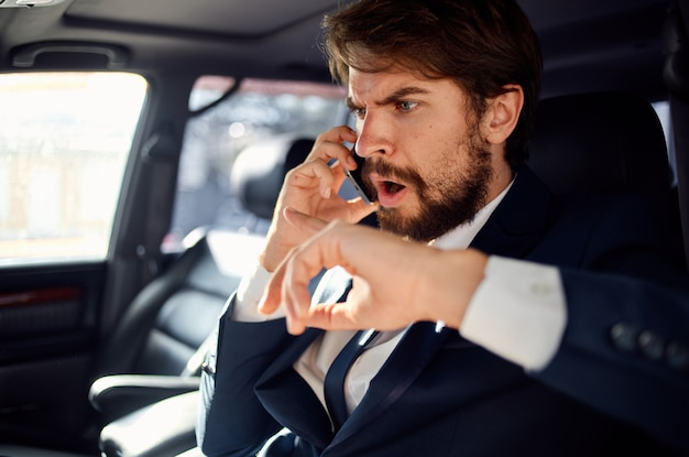 Un uomo in giacca e cravatta in macchina parla al telefono con un passeggero ufficiale