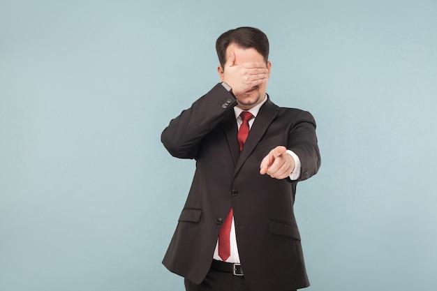 L'uomo in tuta ha gli occhi chiusi e punta il dito verso la telecamera