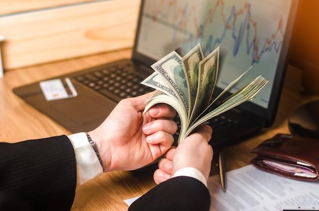 Un uomo in giacca e cravatta conta i soldi su un laptop con grafici economici