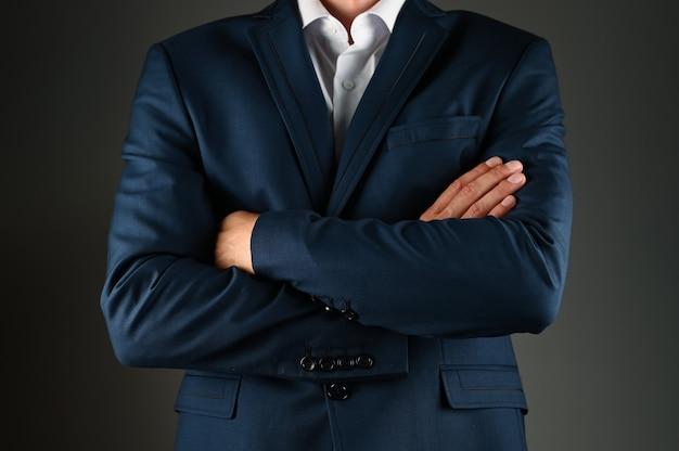 L'uomo in giacca e cravatta incrociò le braccia. un uomo in giacca e cravatta su uno spazio nero. concetto: costruzione nel mondo degli affari.