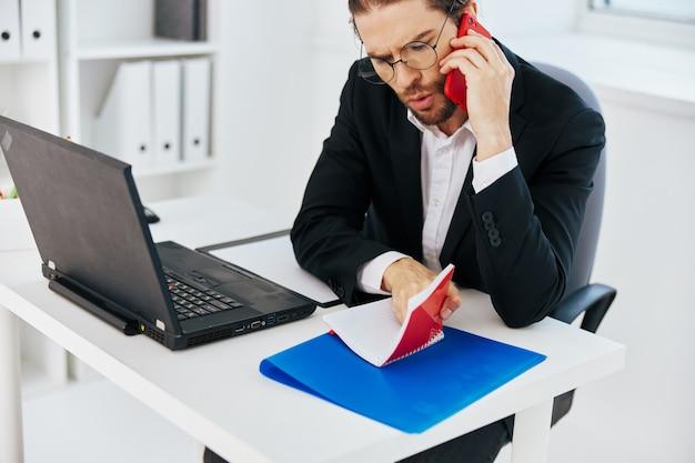 L'uomo in tuta documenta lo stile di vita del laptop dell'ufficio del lavoro