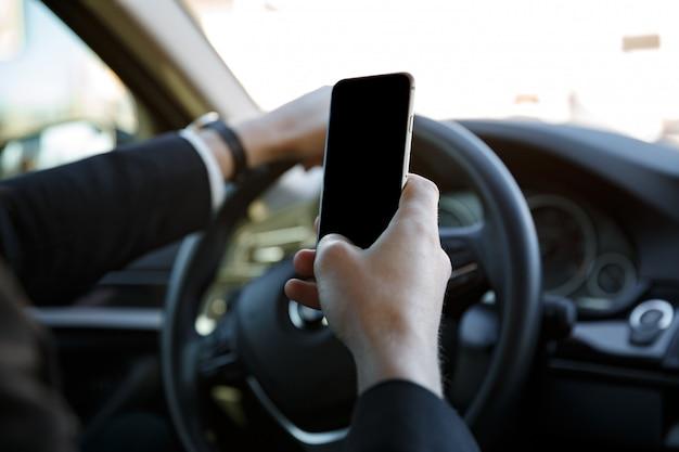 Uomo in vestito che conduce automobile e che tiene telefono cellulare