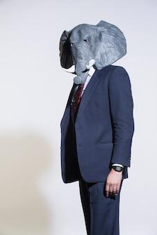 Un uomo in giacca e cravatta e una maschera da elefante su uno sfondo chiaro. sfondo aziendale concettuale