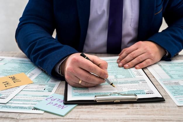 L'uomo in giacca e cravatta compila il modulo fiscale 1040 per gli stati uniti. tempo fiscale. concetto di contabilità