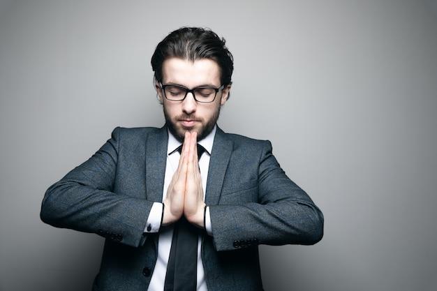Uomo in giacca e occhiali ha unito le mani sul muro grigio