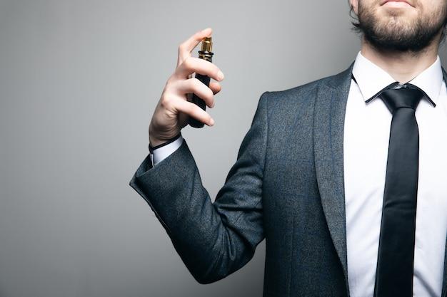 L'uomo in un vestito e occhiali spruzza con profumo su un muro grigio