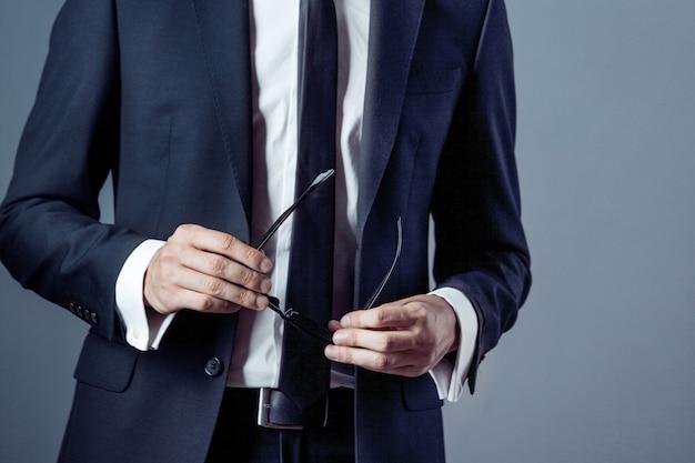 Uomo in vestito su un grigio, primo piano delle mani