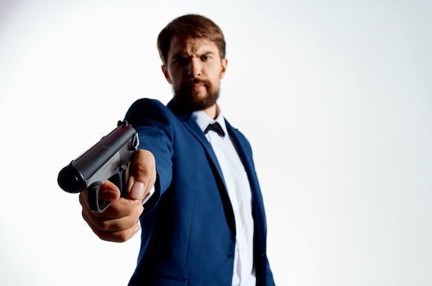 L'uomo con una tuta pistola nelle mani dello sfondo chiaro dell'agente delle emozioni della mafia