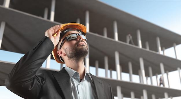 L'uomo in giacca e casco controlla il processo di costruzione.