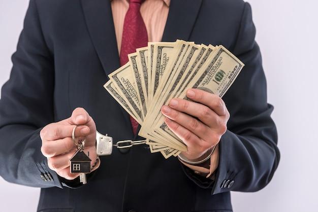 L'uomo in tuta tiene il dollaro e la chiave di casa in manette. corrompere il concetto di corruzione