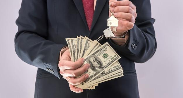 Uomo in tuta tenere dollaro e chiave di casa in manette. corrompere il concetto di corruzione