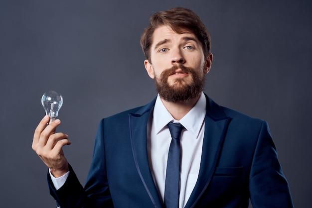Uomo in un vestito che tiene un'innovazione di successo dell'idea della lampada