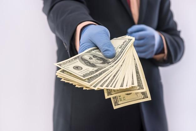 Uomo in tuta che tiene soldi dollari 100 banconote in guanti medici per sicurezza. crisi del coronavirus. covid-19