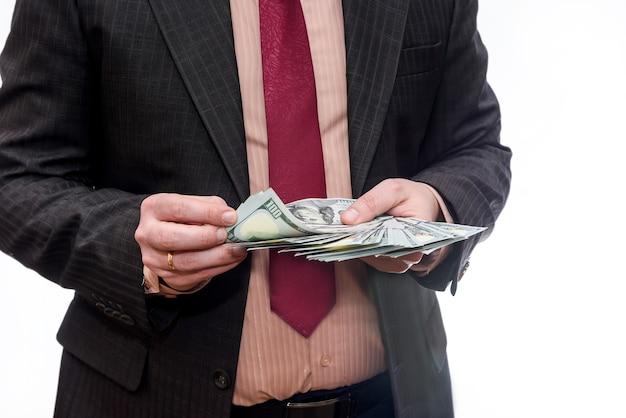 Uomo in vestito che tiene mucchio di banconote in dollari