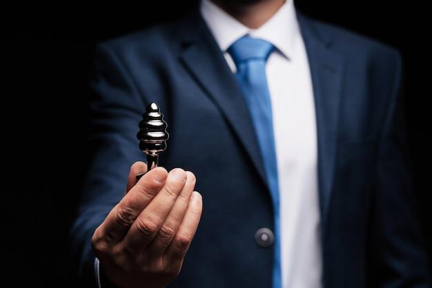L'uomo in giacca e cravatta tiene in mano un plug anale