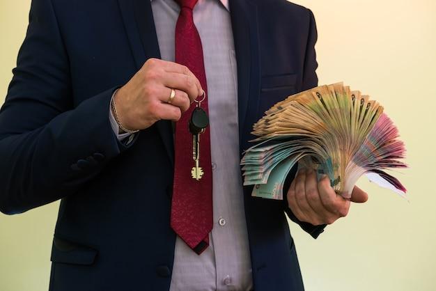 Un uomo in giacca e cravatta tiene una grossa pila di soldi ucraini e mostra il suo reddito. uah. nuove banconote 1000 e 500 grivna